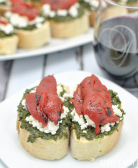 Kale Pesto Goat Cheese Crostini with Roasted Red Pepper + Wines of Garnacha is the perfect pairing for all of your holiday celebrations, parties & gatherings! A quick, easy and festive appetizer and easy drinking wines to enjoy with family and friends. #LoveGarnacha #GarnachaDay #ad